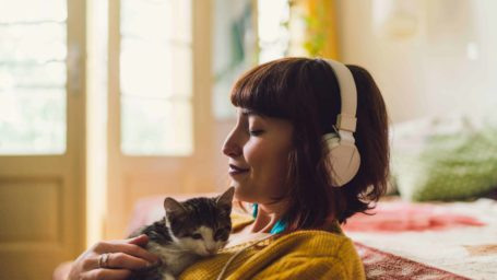 Woman holding kitten while wearing headphones